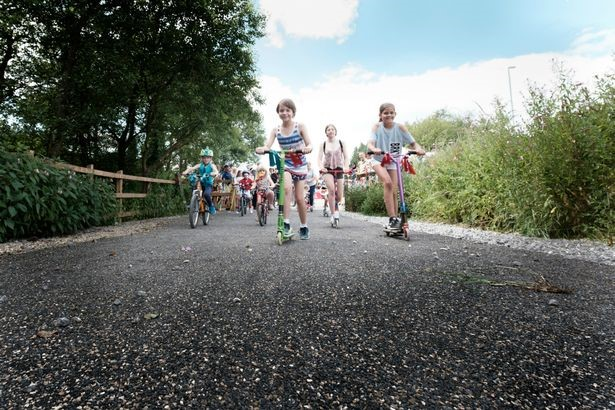 Image of children riding bikes on a cycle route and scooting for visit Rossendale website