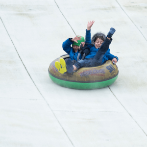 Two children tubing at The Hill - Ski Rossendale